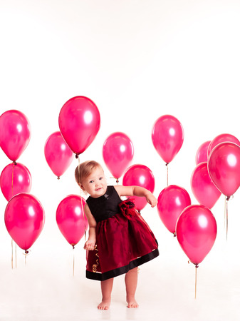12 year old: Smiling baby girl 1-2 year old playing with pink balloons in room over white. Looking at camera. Having fun. Birthday party. Celebration.