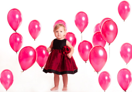 12 year old: Cute baby girl 1-2 year old wearing stylish dress in room with balloons. Looking at camera. Childhood. Birthday party. Celebration.