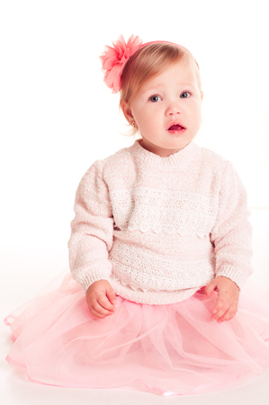 12 year old: Funny baby girl 1-2 year old wearing stylish sweater and skirt over white. Looking at camera. Childhood.