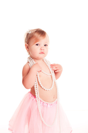 12 year old: Cute baby girl 1-2 year old wearing pearl necklace over white. Looking at camera. Childhood.