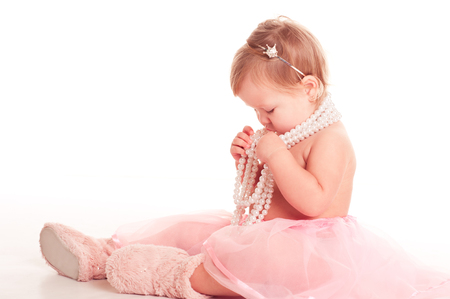12 year old: Baby girl 1-2 year old playing with pearl necklace over white. Sitting on floor in room. Childhood.