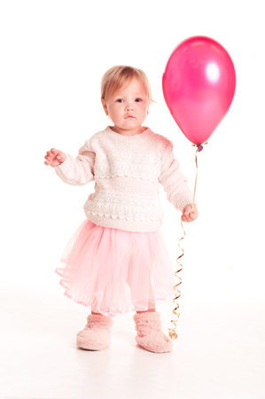 12 year old: Cute baby girl 1-2 year old holding pink balloon over white. Isolated. Looking at camera. Playful. Childhood. Stock Photo
