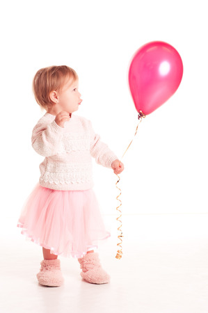 12 year old: Funny baby girl 1-2 year old holding pink balloon over white. Isolated. Playful.