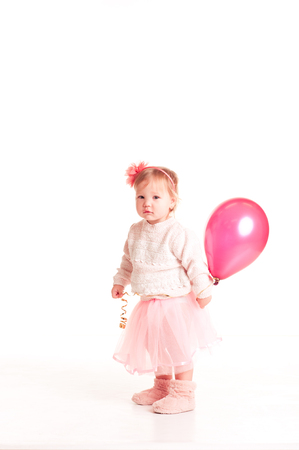 12 year old: Smiling baby girl 1-2 year old holding pink balloon in room over white. Looking at camera. Childhood.
