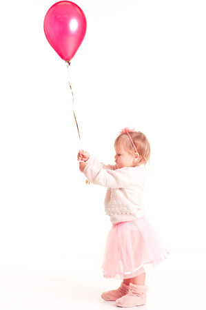 12 year old: Cute baby girl 1-2 year old playing with pink balloon in room over white. Isolated. Childhood.