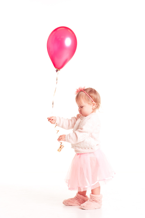 12 year old: Cute kid girl 1-2 year old playing with pink balloon over white. Playful. Childhood.  Stock Photo