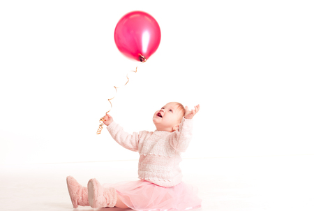 12 year old: Happy baby girl 1-2 year old playing with pink balloon in room over white. Isolated. Happiness.
