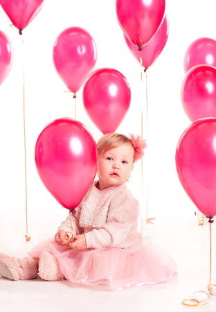 12 year old: Cute baby girl 1-2 year old sitting on floor with pink balloons in room over white. Isolated. Birthday party. Celebration.