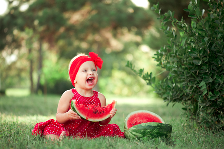 12 year old: Laughing cute girl 1-2 year old eating water melon outdoors. Childhood. Healthy lifestyle.  Stock Photo