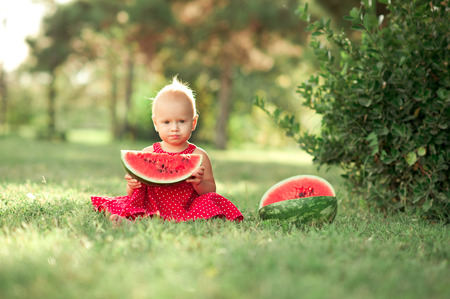12 year old: Cute baby girl 1-2 year old holding watermelon in meadow. Looking at camera. Posing outdoors.