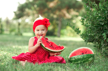 12 year old: Laughing baby girl 1-2 year old eating watermelon outdoors. Looking at camera. Childhood. Stock Photo