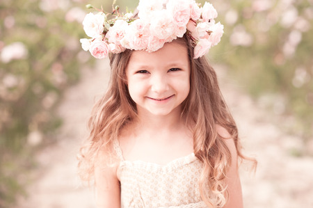 Smiling kid girl wearing wreath with roses outdoors closeup. Looking at camera. Summer time.