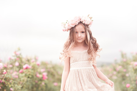 3 year old: Beautiful baby girl 3-4 year old walking in rose garden with wreath of flowers outdoors. Looking at camera. Childhood.