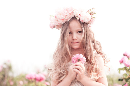 3 year old: Cute baby girl 3-4 year old holding flower rose outdoors. Child standing in meadow. Looking at camera.