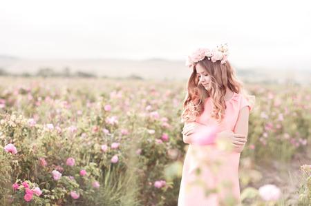 Teen dívka 14-16 let staré představují v růžové zahradě. Nosit stylové šaty a květinový věnec venku.