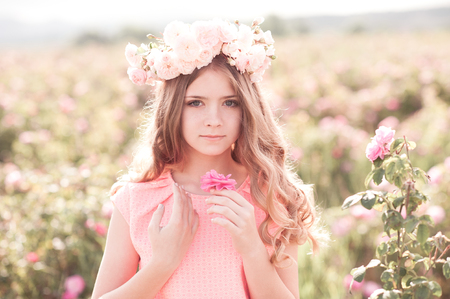 Smiling blonde teen girl posing in rose garden. Wearing flower wreath outdoors. Looking at camera.  Stock Photo