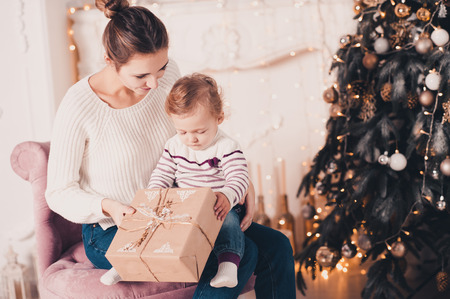 smiling young mother open christmas presents with baby girl 1 year old under christmas tree - Christmas Presents For 1 Year Old
