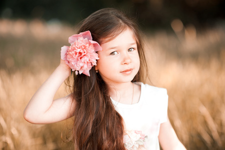 34: Smiling kid girl 3-4 year old wearing flower in hair outdoors. Looking at camera. Childhood.  Stock Photo