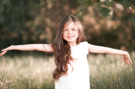 4 5 year old: Smiling kid girl having fun outdoors. Looking at camera. Laughing kid. Childhood.