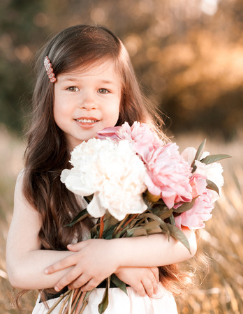 Happy baby girl 4-5 year old holding peonies outdoors. Looking at camera. Childhood.