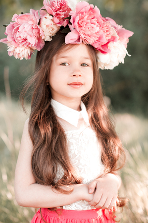 Smiling baby girl 4-5 year old posing with peony wreath outdoors. Looking at camera. Summer season.  Stock Photo