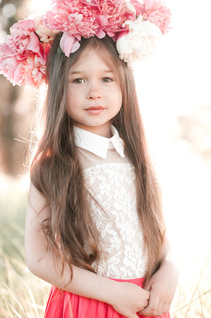 34: Beautiful kid girl 3-4 year old wearing floral hairstyle outdoors. Looking at camera.