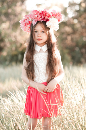 34: Cute baby girl 3-4 year old wearing peony wreath outdoors. Looking at camera. Childhood.