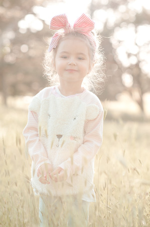 Smiling baby girl 4-5 year old wearing stylish sweater outdoors. Looking at camera. Childhood. Summer time. Stock Photo