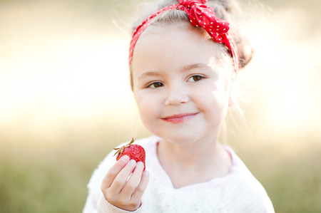 Smiling baby girl 4-5 year old eating fresh strawberry outdoors. Summer season. Childhood.