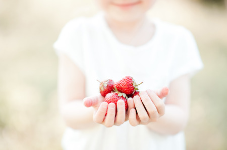 Cute kid girl holding strawberry outdoors. Selective focus. Stock Photo