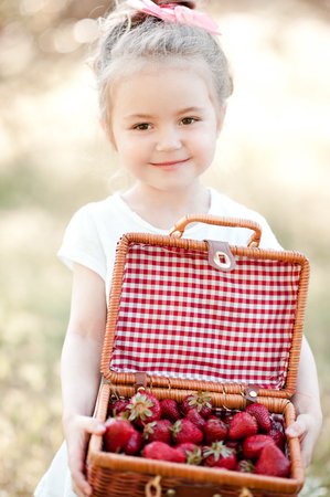 Smiling baby girl holding basket with strawberry outdoors. Looking at camera. Childhood. Stock Photo