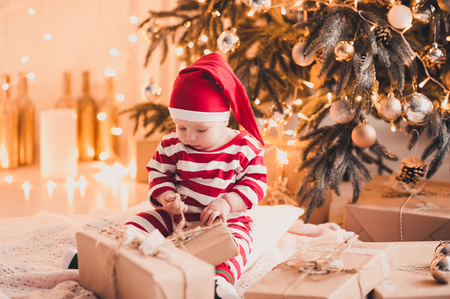 cute baby girl 1 year old open christmas presents sitting on floor under christmas tree in