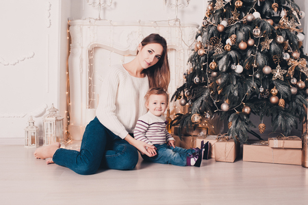 decorate: Young beautiful mother sitting with baby girl under 1 year old in room with Christmas tree and presents. Looking at camera. Celebration. Holiday time.