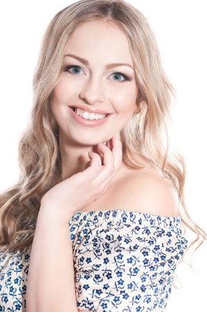 Smiling beautiful blonde girl 20-24 year old over white. Looking at camera. Wearing stylish floral dress. Isolated. Elegance.
