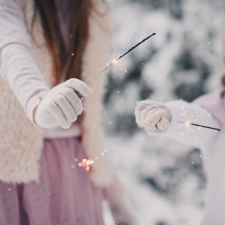 having fun in winter time: Kids playing with sparklers closeup outdoors. Wearing winter clothes and gloves over snow background. Christmas holidays. Childhood.