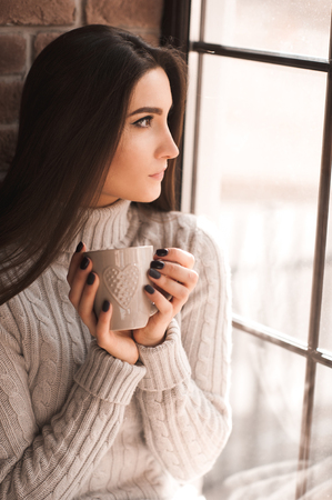 Smiling brunette girl 20-24 year old drinking coffee sitting wearing knitted sweater looking at window. Winter season.