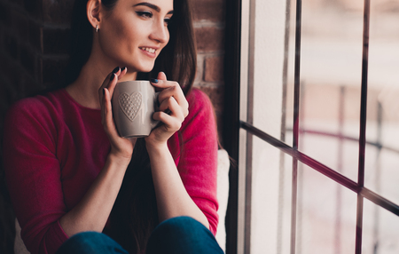 Smiling girl 20-24 year old holding cup of tea sitting on windowsill and looking at window. 20s. Good morning. Focus on cup.