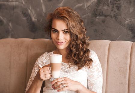 vestidos de epoca: Sonriente niña de 20-24 años de edad de beber café en el café. Con un vestido elegante blanco. Mirando a la cámara. Hora de cafe. Buenos días. Foto de archivo
