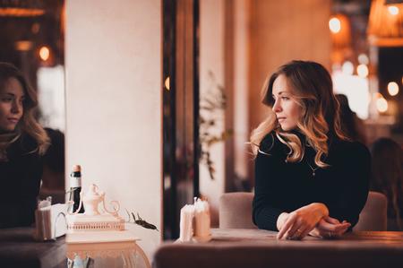 Muchacha rubia hermosa 20-24 años que se sientan en el café que mira la ventana. 20s. Temporada de invierno.