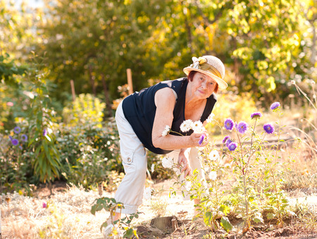 Smiling senior woman 70-80 year old posing with flowers in garden. Looking at camera. 70s.