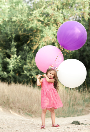 Cute kid girl 4-5 year old holding big colorful balloons outdoors. Looking at camera. Happiness. Celebrating birthday.  Stock Photo