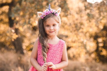 Smiling kid girl 4-5 year old with long hair wearing pink dress and unicorn headband outdoors. Looking at camera. Childhood.