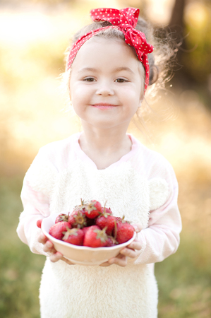 Happy kid girl 4-5 year old holding white bowl with fresh strawberries over nature background. Wearing trendy headband and sweater outdoors.Looking at camera. Childhood.