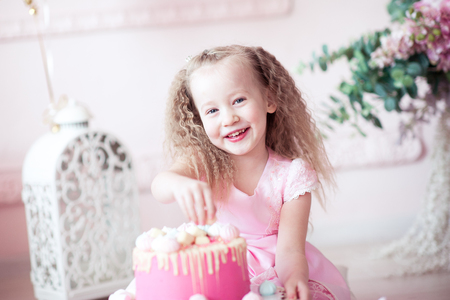 3 year old: Smiling kid girl 3-4 year old eating birthday cake sitting on floor in room. Looking at camera. Celebration. Happiness.