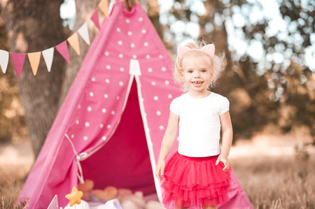 Cute blonde baby 3-4 year old playing outdoors. Happiness. Childhood.