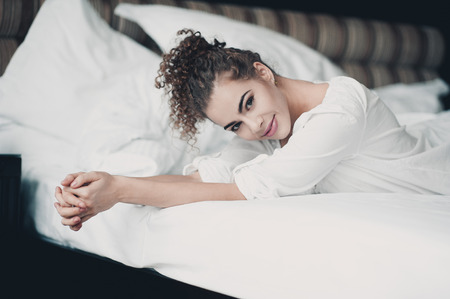 Smiling beautiful girl 20-24 year old resting in bed in hotel room. Looking at camera. Good morning.