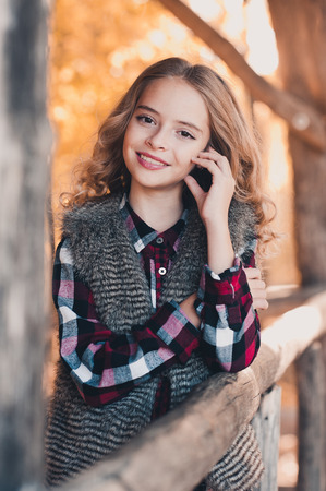 Smiling teen blonde girl 12-14 year old wearing casual clothes outdoors. Looking at camera. Teenager hood.