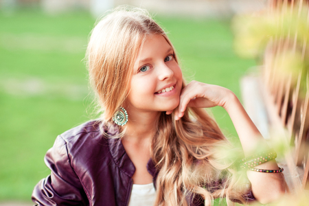 Smiling teen girl 14 -16 year old wearing leather jacket outdoors. Looking at camera. Summer season.  Stock Photo