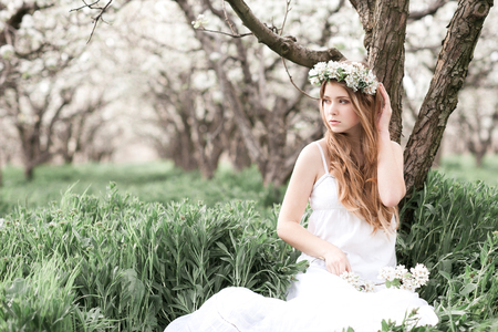 Beautiful teenage girl 14-16 year resting in orchard. Wearing elegant dress and flower wreath outdoors. Looking away.
