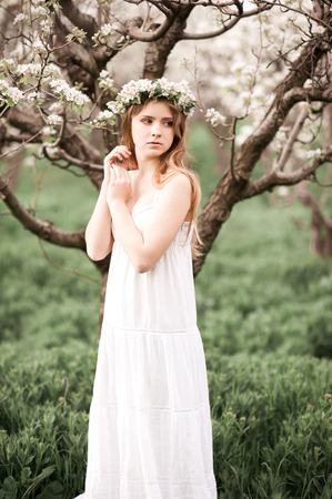 Beautiful teen girl 14-16 year old wearing elegant white dress and wreath with flowers in pear orchard. Looking away.  Stock Photo